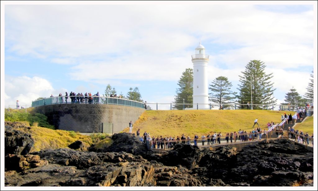 Lighthouse at the backdrop, onlookers await for the Blowhole to erupt...
